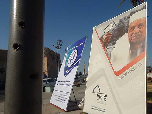 Libya election poster with a post with bulletholes in it in the foreground