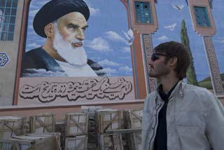 Matthew VanDyke with a mural of Grand Ayatollah Khomeini in Iran