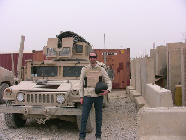 journalist matthew vandyke working as a war correspondent next to a military humvee at fob marez in mosul iraq