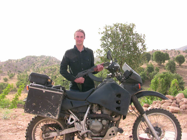 matthew vandyke with his kawasaki klr650 motorcycle and ak-47 in iraq
