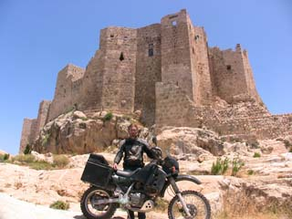 Matthew VanDyke with his Kawasaki KLR650 motorcycle at the Castle of Assassins in Musyaf Syria