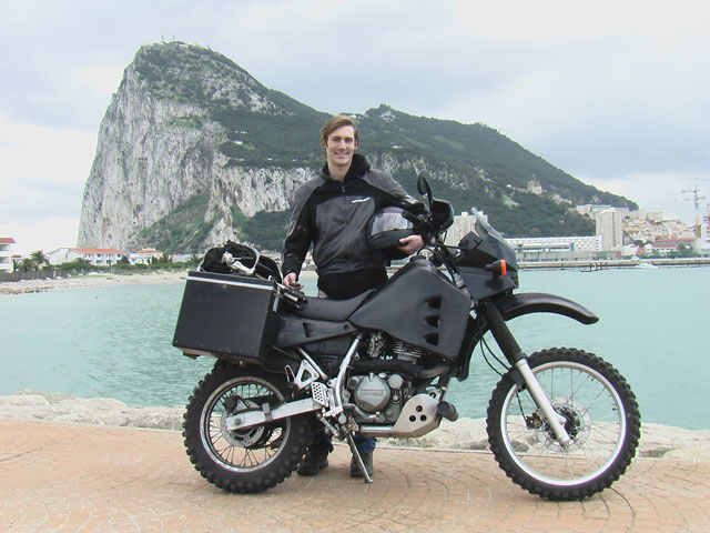 Matthew VanDyke in front of Gibraltar with his Kawasaki KLR 650 motorcycle