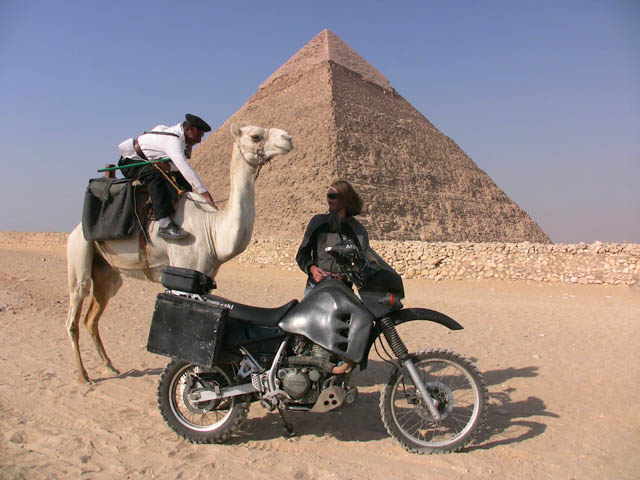 Matthew VanDyke with his Kawasaki KLR650 motorcycle and an Egyptian police officer on a camel in front of a pyramid in Giza Egypt