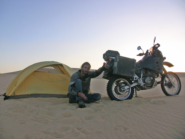 Matthew VanDyke with his Kawasaki KLR650 motorcycle and tent camping on a sand dune in the desert in Egypt