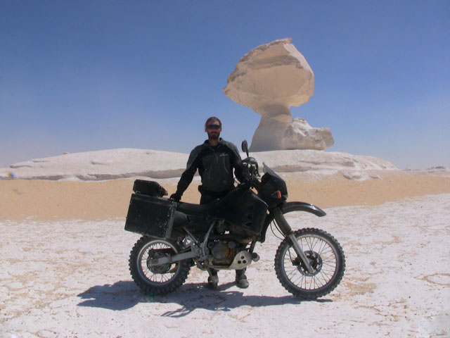 Matthew VanDyke with his Kawasaki KLR650 motorcycle in front of a mushroom rock formation in the White Desert of Farafra Egypt