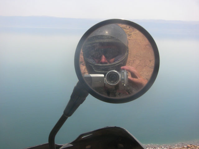 Matthew VanDyke reflection in his motorcycle mirror in Jordan while photographing Israel and the Dead Sea