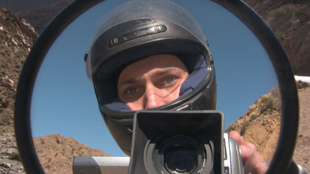 Matthew VanDyke reflection in his motorcycle mirror in Morocco