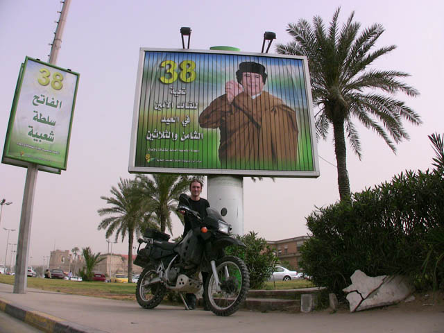 matthew vandyke with his kawasaki klr650 motorcycle in front of a muammar gaddafi billboard in tripoli libya