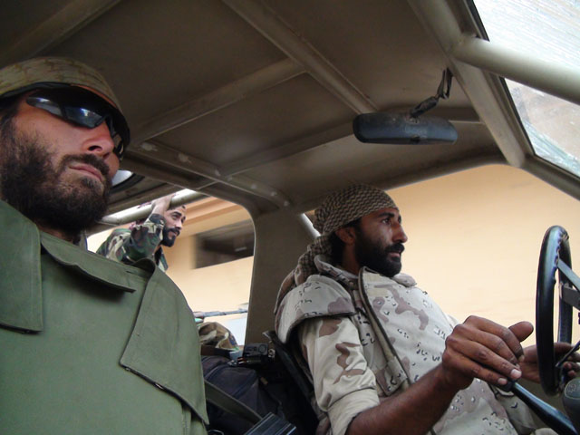 Matthew VanDyke and Nouri Fonas riding in a KADDB Desert Iris 4x4 during the Libyan Civil War
