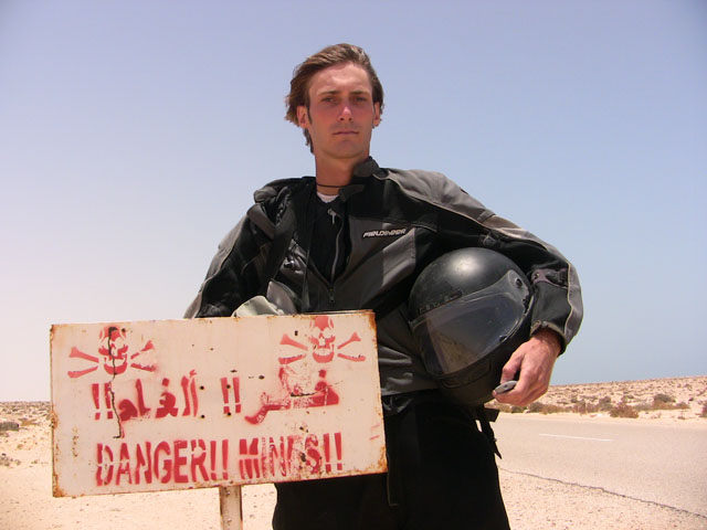 Matthew VanDyke in his motorcycle gear next to a land mine warning sign in Western Sahara