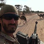 Matthew VanDyke in the jeep turret with his DShK machine gun and camels in the background during the war in Libya